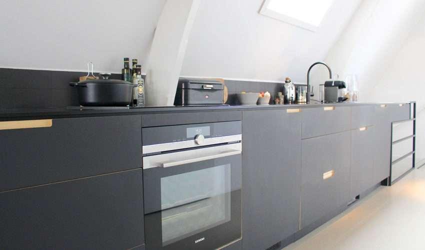 Zwarte keuken onder een schuin dak